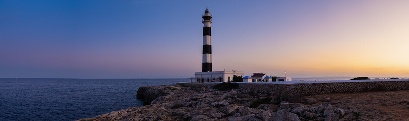 Blue hour view of the Cap Artrutx Lighthouse or Artrutx Lighthouse, an active 19th century lighthouse located on the low-lying headland of the same name on the Spanish island of Menorca.