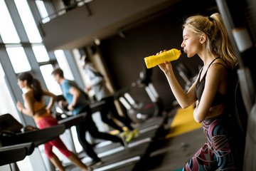 Young woman drinking water in gym after workout