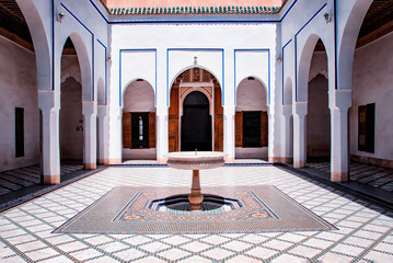 Courtyard at El Bahia Palace, Marrakech, Morocco. there are white walls and columns with blue signs and white fountain.