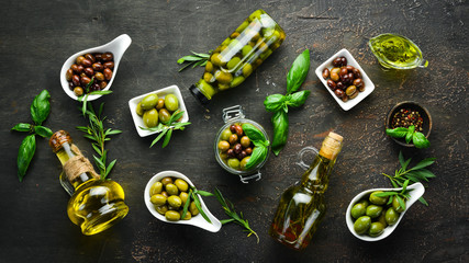 Olives, olive oil, spices and herbs on the Rustic background. Top view. Free space for your text.