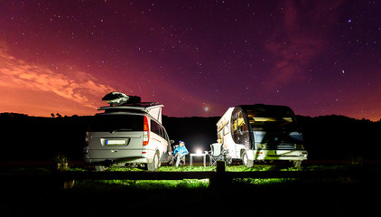 Campervans are parked on a beach at night under stars.