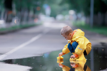 a boy plays boats in a puddle / childhood, walk, autumn game in the park, a child on a walk