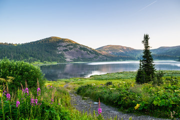 View on mountain lake with hills and green forest during sunrise. Ergaki national park, Siberia, Russia