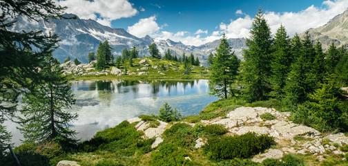 Górski krajobraz z jeziorem i zielonymi drzewami wokół. Poczucie wolności. Park Narodowy Gran Paradiso, jezioro Bellagarda, Ceresole Reale, Piemont, Włochy