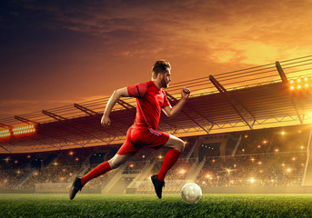 Professional soccer player in action with a ball on a soccer field. Dramatic night sky