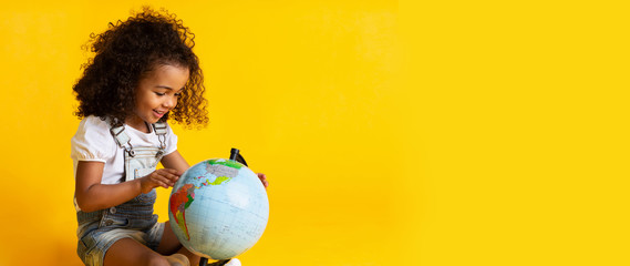 Early education. Little girl pointing to world globe
