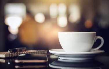 Zbliżenie biała filiżanka kawy z smartphone, notatnikiem i piórem na stole w kawiarni. Tło światło, niewyraźne i bokeh