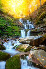 Autumn mountain waterfall stream in the rocks with colorful fallen dry leaves, landscape