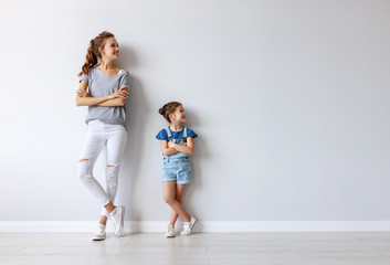 happy family mother (big sister) and child daughter near an empty wall.