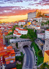 Porto, Portugal. Top view aerial cityscape panorama of old town during beautiful evening sunset. Road street with tunnel under hill with houses with red roofs.