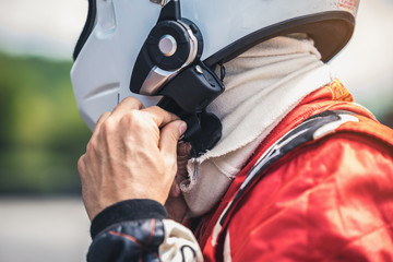The racer's hand is wearing a helmet strap for safety in the race.