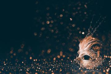 Luksusowa wenecka maska na ciemnym złotym bokeh tle. Nowy rok i święto Bożego Narodzenia celebracja projekt transparent.