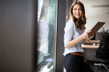 Happy woman manager holding tablet and standing in modern office