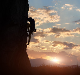 Side view of strong rock climber at dawn. Male silhouette on high rocky wall having extreme outdoors activity. Concept of perseverance and never give up. Sunrise sky with clouds and copy space