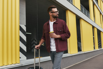 Tourist. Handsome bearded man in casual wear and eyeglasses holding a disposable cup and carrying his luggage while walking through the city street