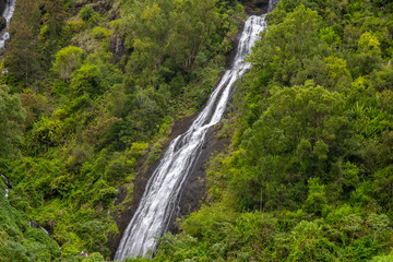 Waterfall on a green mountain at french island Reunion in the indian ocean