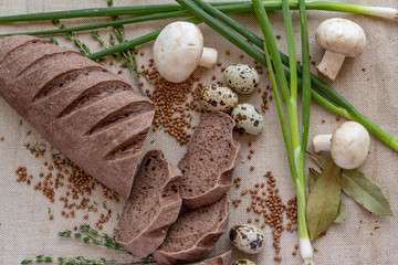composition of dark sliced bread with scattered buckwheat, sprigs of rosemary, fresh mushrooms, quail eggs and green onions on baking canvas