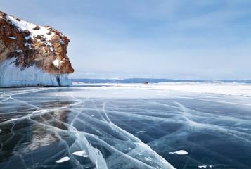 Jezioro Bajkał w lutym. Samochód jedzie wzdłuż zamarzniętej Cieśniny Małej Morskiej w pobliżu skał wyspy Olkhon. Zimowa podróż samochodem po lodzie jeziora. Piękny zimowy krajobraz