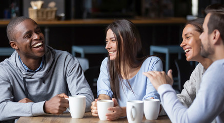 Multiracial friends girls and guys having fun laughing drinking coffee