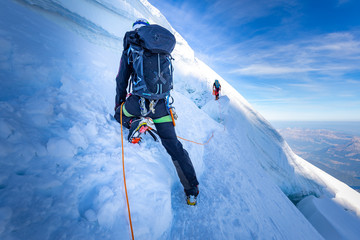 Two alpinists mountaineers climbing over ice crevasse.