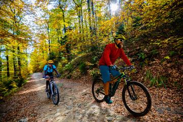 Kolarstwo, para rowerzystów górskich na szlaku rowerowym w lesie jesienią. Kolarstwo górskie w jesień krajobraz lasu. Mężczyzna i kobieta na rowerze MTB płyną pod górę szlaku.