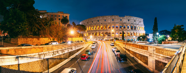 Rome, Italy. Colosseum Also Known As Flavian Amphitheatre. Traffic In Rome Near Famous World Landmark In Evening Time.
