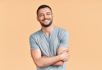 Happy smiling handsome man with crossed arms looking to camera over beige background