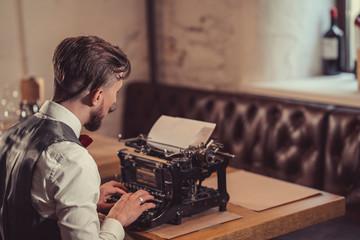 Working man typing on a retro typewriter