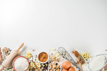 Ingredients for autumn winter festive baking - flour, brown sugar, eggs, chocolate drops, butter, cinnamon on stone or concrete background.Top view copy space.