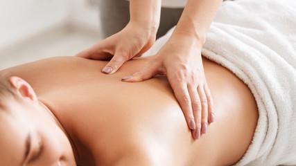Pielęgnacja ciała. Młoda dziewczyna o masażu, relaks w salonie spa