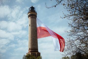 Old Brick Stone Lighthouse with polish national flag