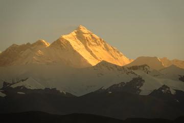 Picturesque view of orange hued evening sunbeams illuminating Mount Everest.