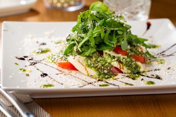 Fresh caprese salad with pesto on plate, food close-up