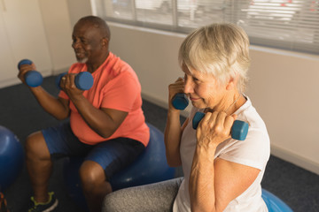 Senior people exercising with dumbbells at home