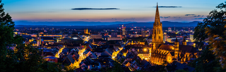 Germany, XXL panorama of city freiburg im breisgau from above in summer in magical twilight atmosphere after sunset