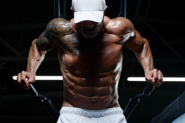 Handsome athletic men pumping up muscles push-ups on uneven bars workout fitness exercises and bodybuilding concept background - muscular bodybuilder fitness men doing bars exercises in gym naked