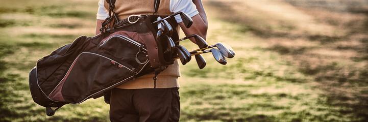 Obsługuje nieść golfową torbę podczas gdy stojący na polu