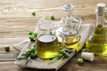 oliwa z oliwek i świeże zielone oliwki na drewnianym tle