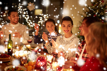 winter holidays and people concept - happy friends with sparklers celebrating christmas at home feast over snow