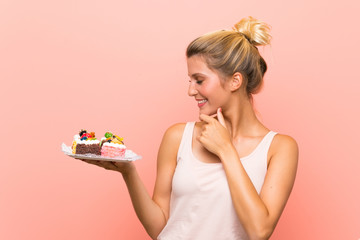 Young blonde woman holding lots of different mini cakes thinking an idea