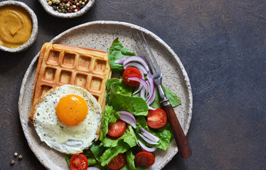 Belgian waffles with egg and salad for breakfast in a plate on the kitchen table. View from above.