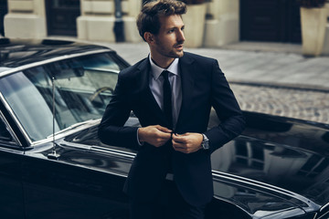 Handsome man in black suit with old classic car