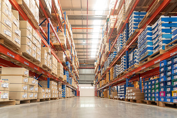 Rows of shelves with goods boxes in huge distribution .warehouse at industrial storage factory.