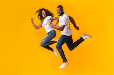 Playful african couple is running in the air