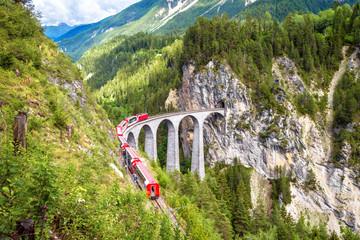 Landwasser Viaduct in Filisur, Switzerland. It is famous landmark of Swiss. Mountain landscape with red train of Bernina Express on high bridge. Scenic view of amazing Alpine railway in summer.