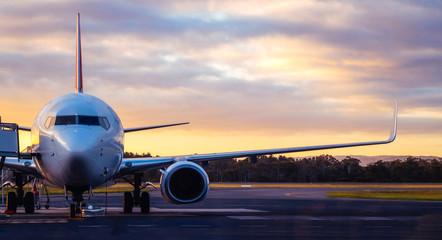 Zmierzchu widok samolot na lotniskowym pasie startowym pod dramatycznym niebem w Hobart, Tasmania, Australia. Technologia lotnicza i koncepcja podróży po świecie.