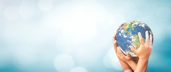 World environment day concept: Earth globe in family hands over blurred nature background. Elements of this image furnished by NASA