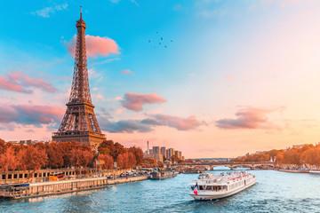 Główną atrakcją Paryża i całej Europy jest wieża Eiffla w promieniach zachodzącego słońca nad brzegiem Sekwany z wycieczkowymi statkami turystycznymi