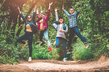 Group of happy Asian teenage adventure traveler trekkers group jumping together in mountain at outdoor forest background. Young hiker friends supporting each others as survival team travel and success