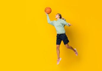 Teenager girl basketball ball jumping over isolated yellow background.